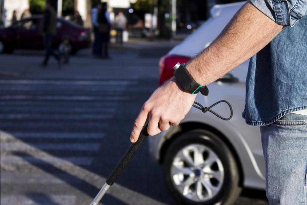 Billede af Sunu Band monteret på håndled og med den hvide stok, ude i trafikken.