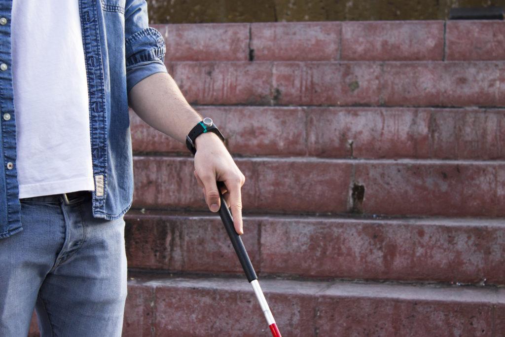 Billede af Sunu Band monteret på håndled som står med den hvide stok i hånden foran en trappe.