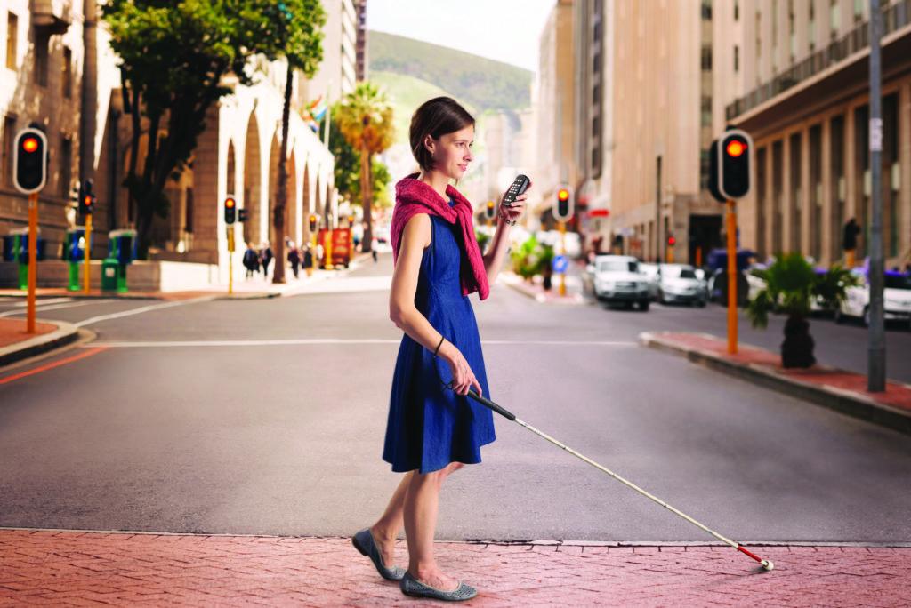 Billede af kvinde der krydser gaden med Den Hvide Stok og Victor Reader Trek i hånden.