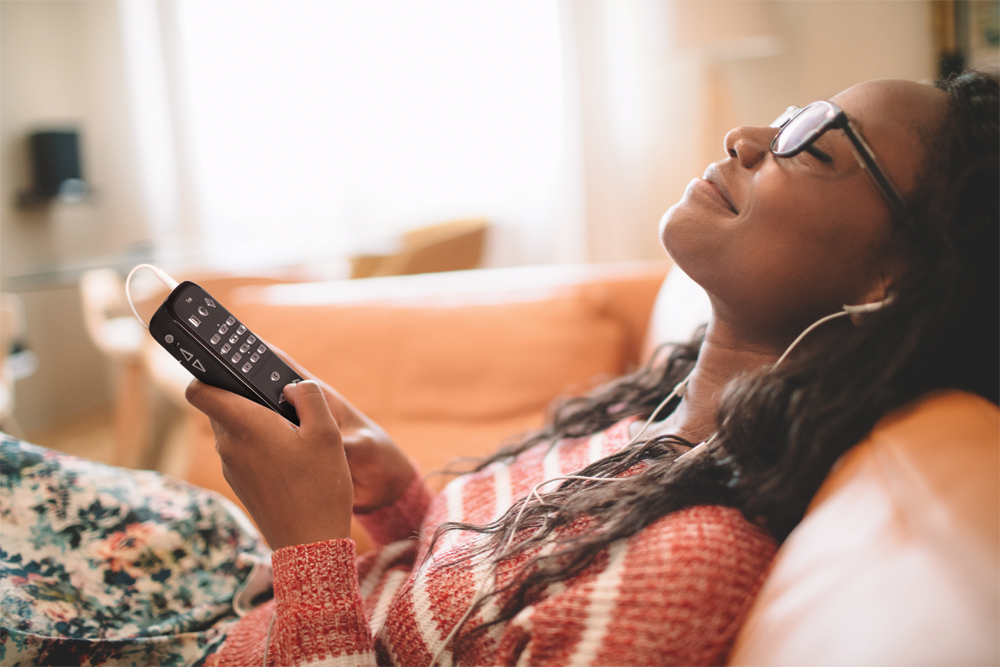 Billede af kvinde med Victor Reader Trek som slapper af og lytter til musik.